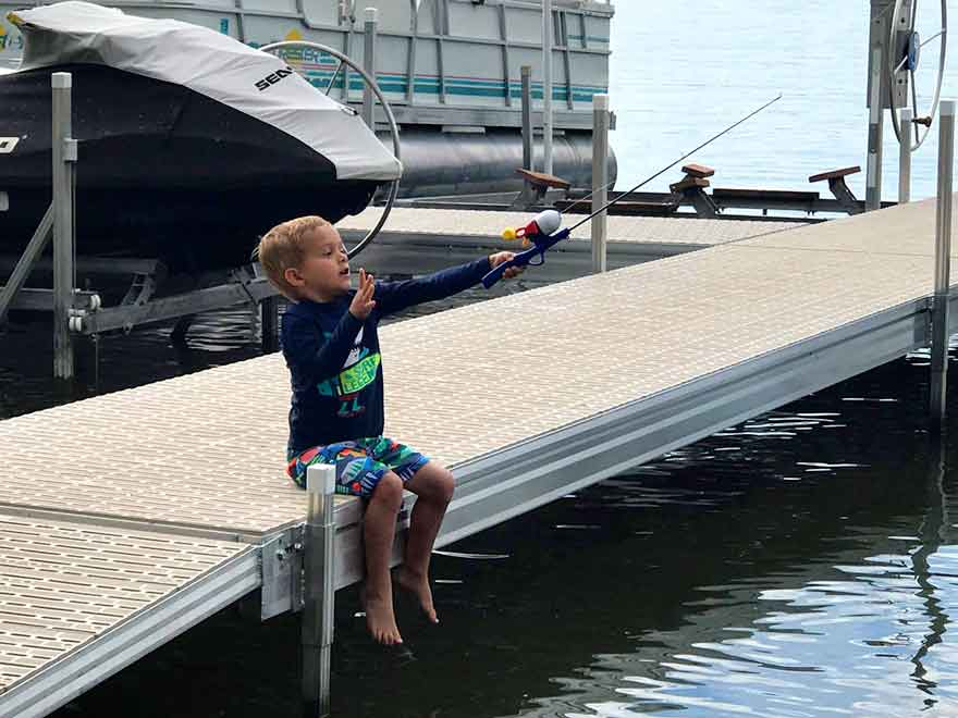 Young boy fishing off the dock at Barrett Lake Resort and Campground